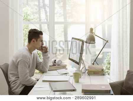 College Student Using Computer At Home