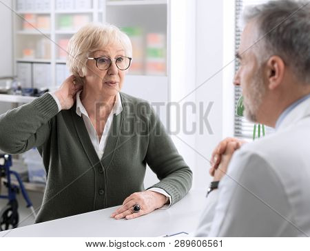 Senior Lady With Neck Pain In The Doctor's Office