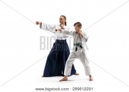 19fbace5d451e Man and teen boy fighting at Aikido training in martial arts school. Healthy  lifestyle and sports concept. Fightrers in white kimono on white background.