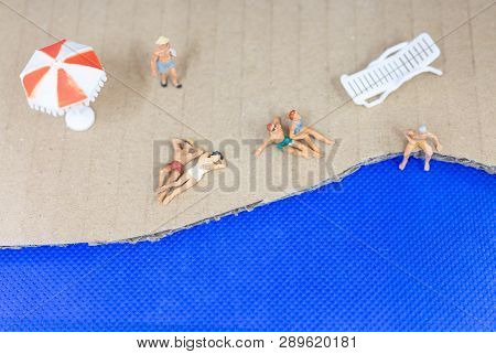 Miniature People Wearing Swimsuit Relaxing On The Beach With Blue Background