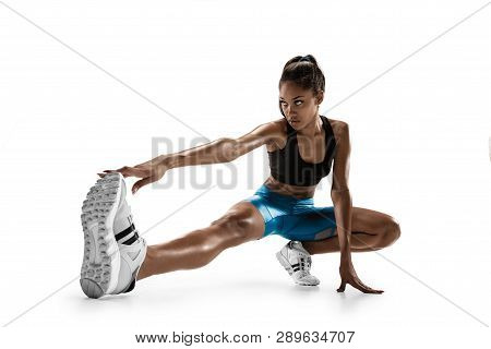 Young African Woman Warming Up Before Run Isolated On White Studio Background. One Female Runner Or