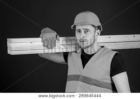 Man In Helmet, Hard Hat And Protective Gloves Holds Wooden Beam, Blue Background. Wooden Materials C