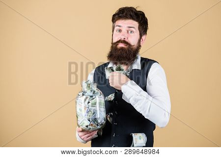 Personal accountant. Businessman with his dollar savings. Richness and wellbeing. Security and cash money savings. Banking concept. Man bearded guy hold jar full of cash savings. Financial insurance poster