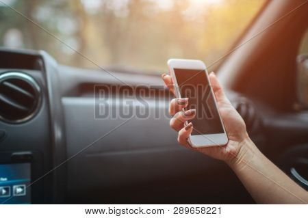 Eautiful Woman Smiling While Sitting On The Front Passenger Seats In The Car. Girl Is Using A Smartp
