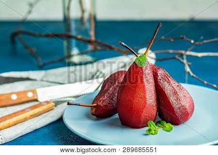 Pears In Wine. Traditional Dessert Pears Stewed In Red Wine With Chocolate Sauce On Plate On Blue Co