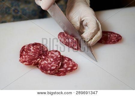 Mens Hands Cut Sausage Salami On A White Cutting Board, Close-up