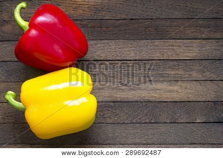 Red And Yellow Sweet Peppers On Wooden Table With Copy Space
