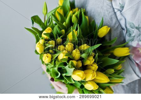 Girl Florist Holding A Bunch Of Yellow Tulips. Floristic. Gray Background