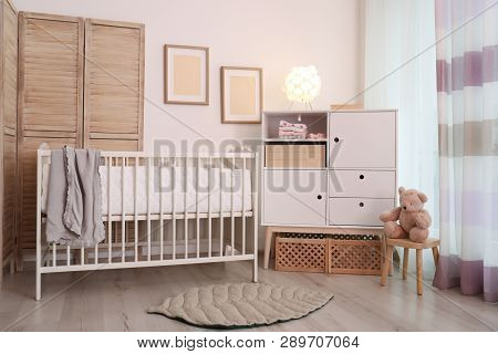 Modern room interior with crib and wooden crates under cupboard. Eco style poster