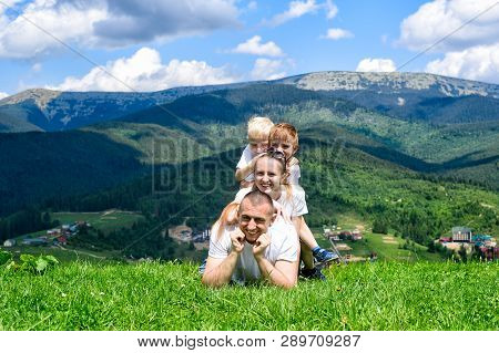 Happy Family: Joyful Father, Mother And Two Sons Are Lying On The Green Grass Against The Background