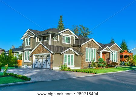 New Family House In Sunset Light. New House With Paved Driveway On Blue Sky Background