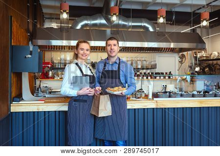 Smiling Young Man And Woman Using Tablet At Small Eatery Restaurant - Happy Business Owners In Apron