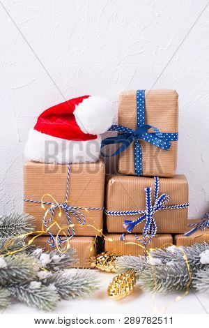 Stack Of Wrapped Boxes With Presents, Red Santa Hat, Fir Tree Branches And Fairy Lights On White Tex