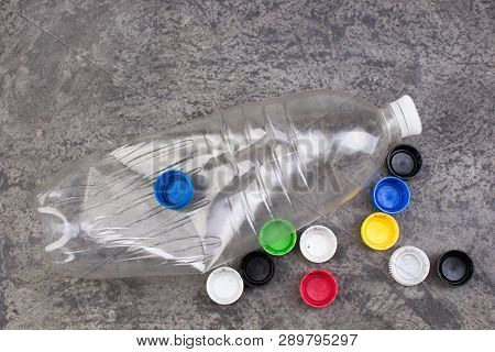 One Empty Used Plastic Bottles, Many Plastic Covers On Bitonny, Gray Background.