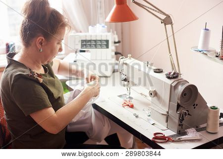 Clothier Sitting In Atelier, Stitching White Dress With Hands And Needle. Seamstress Workplace With