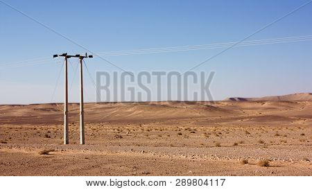 Electric power poles in desert of Jordan. High voltage powerlines. Early morning in wilderness after sunrise. poster