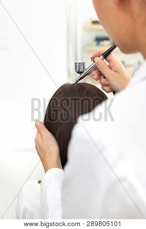 Oxygen bioinfusion of the scalp and hair.A hair treatment. A woman in a trichological office.