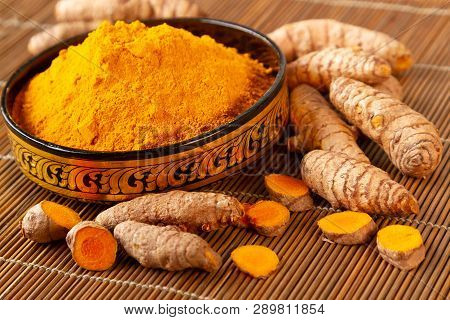 Close Up Of  Turmeric Powder And Fresh Roots In Asian Bowl. Selective Focus On Turmeric Powder