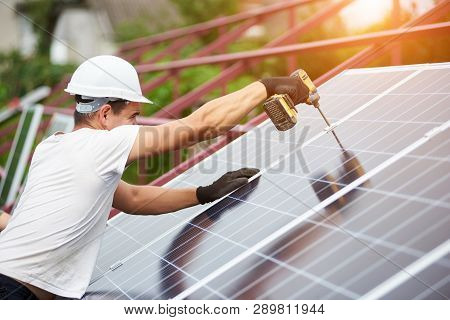 Professional Technician Working With Screwdriver Connecting Blue Shiny Solar Photo Voltaic Panel To