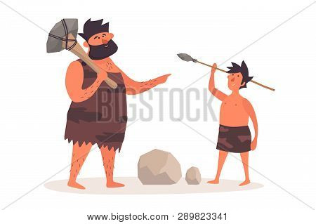 A Primitive Man With A Homemade Ax Teaches A Boy To Throw A Spear. Prehistoric People Dressed In Pel