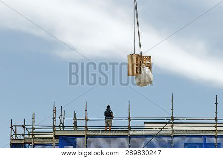 Gosford, New South Wales, Australia - January 31, 2019:  A Working Tower Crane Lifting A Load With A