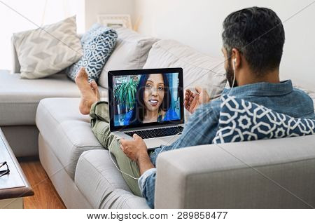 Rear view of husband relaxing on couch while talking to his wife using laptop at home. Mature man lying on sofa and indian woman communicate through video chat on laptop.