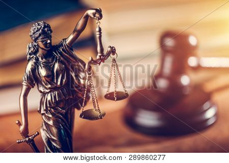 Law and justice concept - Themis statue, judge hammer and books. Courtroom.