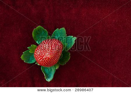 Strawberry From Above With Green Leaves On Red