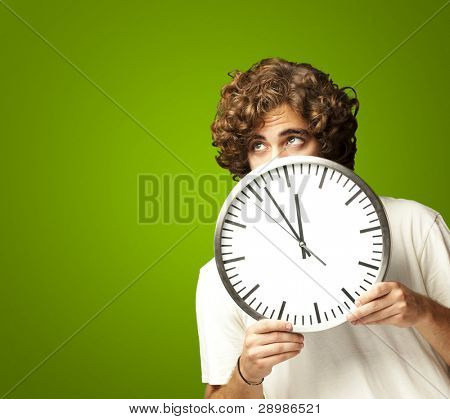 scared young man hidden behind a clock against a green background poster