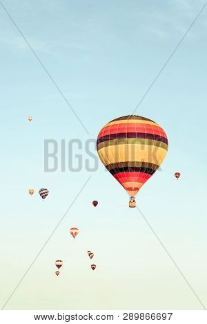 Many Colorful Hot Air Balloons Flying In The Distance. Retro Styled Image.