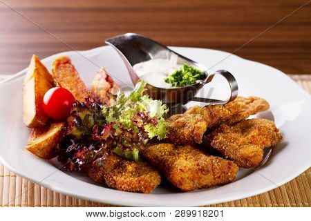 Wiener Schnitzel With Grilled Potato And Dressing On White Plate
