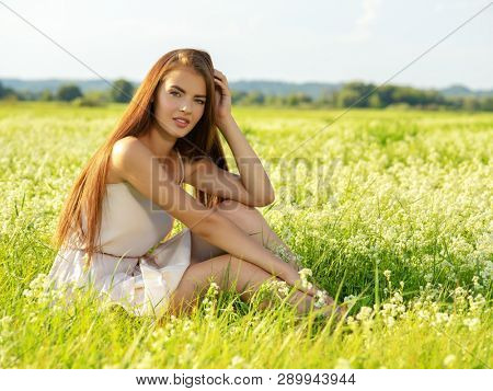 Beautiful young woman on nature over summer field background.  Beautiful girl is on nature on the spring wildflowers background.  Portrait of a Brunette girl with long brown hair - poses on nature