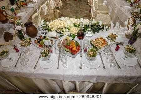 Beautiful table setting with crockery and flowers for a party, wedding reception or other festive event. Glassware and cutlery for catered event dinner. poster