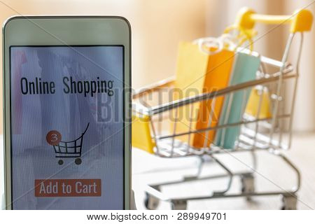 Smart Phone With Goods And Text Add To Cart On Screen And Paper Shopping Bags In Trolley Behind. Con