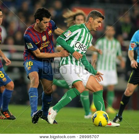 BARCELONA - JAN, 15: Salva Sevilla(R) of Real Betis vies with Sergio Busquets(L) of FC Barcelona during the Spanish league match at the Camp Nou stadium on January 15, 2012 in Barcelona, Spain