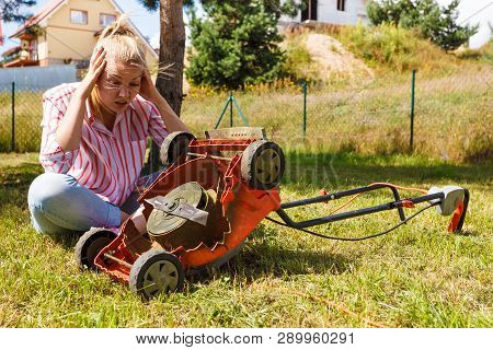 Gardening. Female Person Gardener Mowing Green Lawn With Lawnmower, Having Problem With Broken Mower