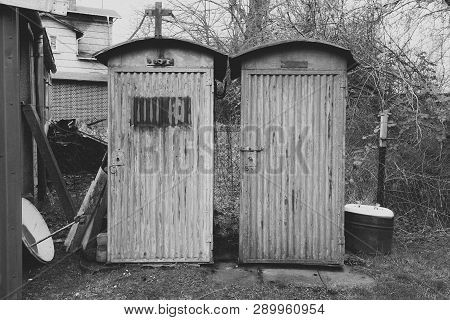 Two Old Rusty Metal Toilet Houses With Stands Side By Side
