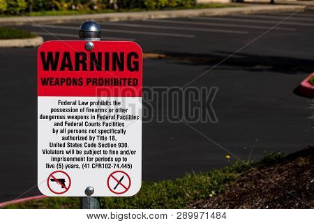 Warning Weapons Prohibited Sign In Front Of A Parking Lot In Daylight