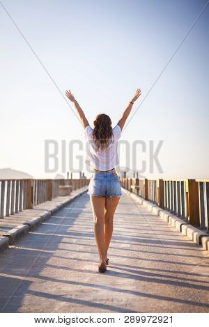 Happy Young Woman Enjoying Freedom With Open Hands