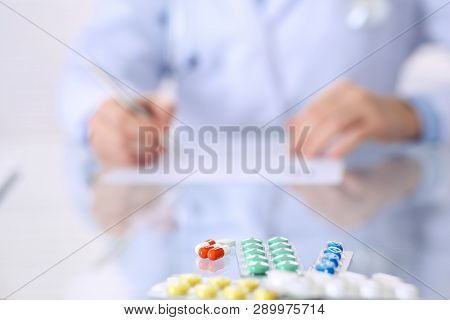 Unknown Woman Doctor At Work At Hospital. Pills At Glass Table. Young Female Physician Write Prescri