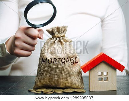 A Female Hand Is Holding A Magnifying Glass Over A Money Bag With The Word Mortgage And A Wooden Hou