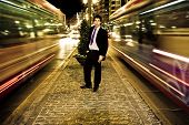 Businessman in night urban scenery, blurred motion. poster