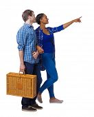 Back view of interracial going couple with a picnic bag who points somewhere. Two students go to the lecture. Isolated over white background. Couple with a suitcase for a picnic considering  poster