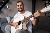 Photo of european man 30s wearing casual t-shirt playing acoustic guitar while sitting on sofa in apartment poster