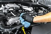A man cleaning car engine with microfiber cloth. Car detailing or valeting concept. Selective focus. Car detailing. Cleaning with sponge. Worker cleaning. Car wash concept solution to clean poster