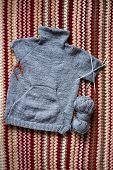Incomplete knitting gray sweater for child with needles poster