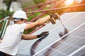 Professional technician working with screwdriver connecting blue shiny solar photo voltaic panel to metal platform on warm sunny summer day. Stand-alone exterior solar panel system installation. poster
