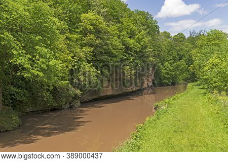 Verdant Green Trees Above A Cliff Lined Stream In White Pines State Park In Illinois