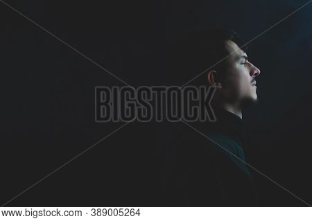 Young Man In The Dark. Male Profile Portrait On The Black Background