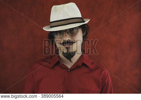 Male Portrait In Eyeglasses. Young Man With Hat In Red Shirt On The Red Background